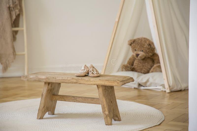 Hölzerner Schemel mit Schuhen auf weißer runder Wolldecke Kind-` s im Rauminnenraum mit Plüschspielzeug im Zelt stockfotografie
