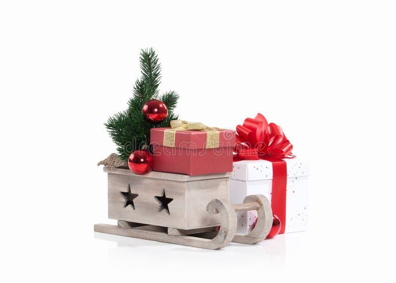 Hölzerner Schlitten mit den Weihnachtsgeschenken lokalisiert auf Weiß lizenzfreies stockfoto