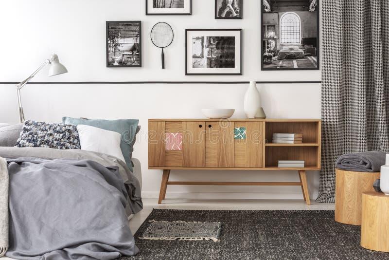 Hölzerner Schrank der Weinlese nahe bei Königgrößenbett mit Kissen und Decke im modischen Schlafzimmerinnenraum stockbild