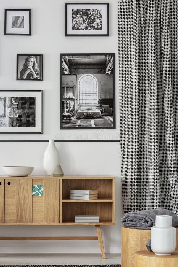 Hölzerner Schrank gegen weiße Wand mit Galerie von Plakaten im hellen Wohnzimmerinnenraum Reales Foto stockfotografie