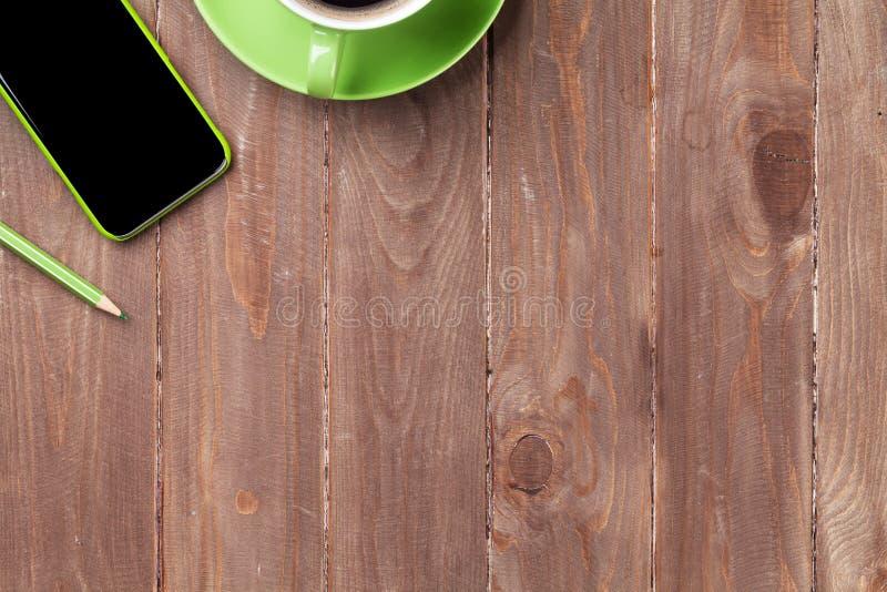 Hölzerner Schreibtisch des Büros mit Smartphone und Kaffee lizenzfreie stockfotografie