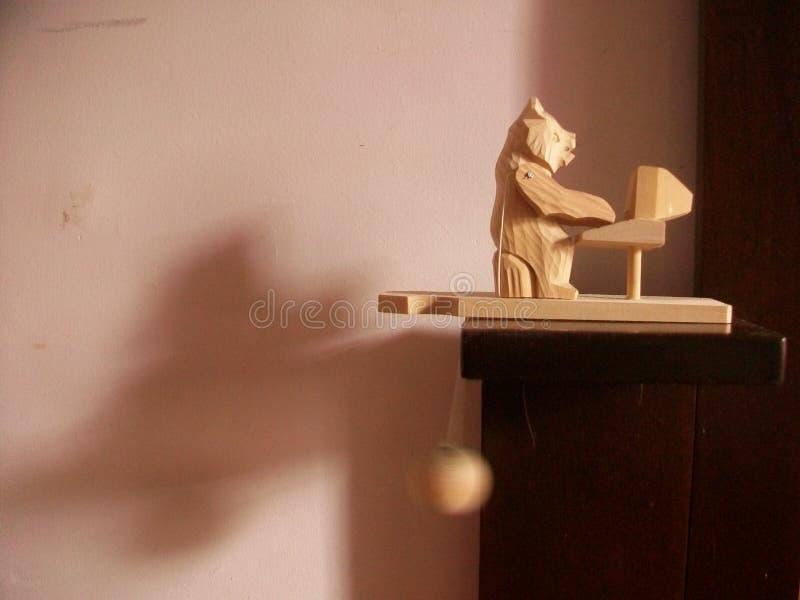 Hölzerner Spielzeugbär unter Verwendung eines Laptops lizenzfreie stockfotos