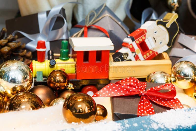 Hölzerner Spielzeugzug als Weihnachtsgeschenk mit glänzendem Flitter, Feiertagshintergrund lizenzfreies stockfoto