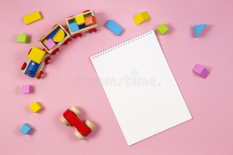Hölzerner Spielzeugzug, rotes Auto, bunte Würfel und weißes leeres offenes Notizbuch auf rosa Hintergrund lizenzfreie stockfotos