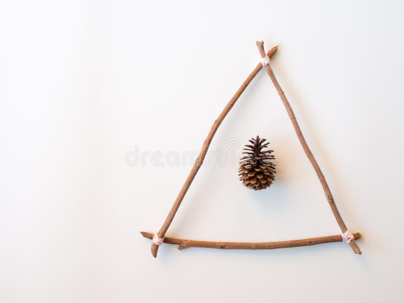 Hölzerner Stock in der Dreieckform und Kiefernkegel für Weihnachtsidee stockfotografie