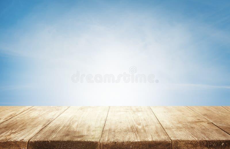 Hölzerner Tischplatte-Hintergrund, leerer hölzerner Schreibtisch über blauem Himmel lizenzfreie stockfotos
