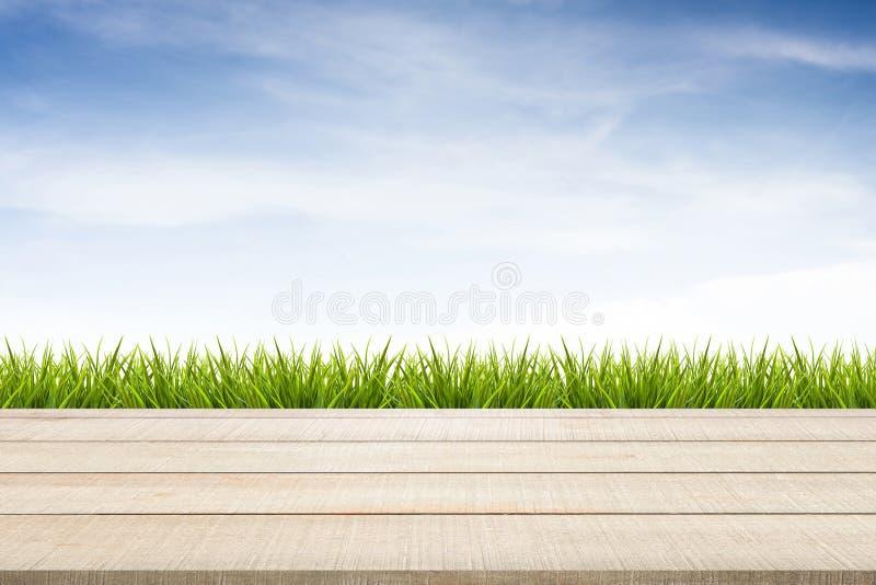 Hölzerner Tischplatteplatten-, Gras- und Himmelhintergrund lizenzfreies stockbild