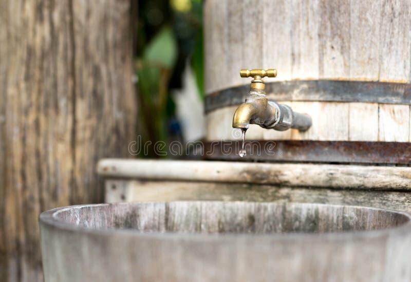 Hölzerner Wasserbehälter des Konzepteinsparungswassers mit goldenem Hahn und in s stockbilder