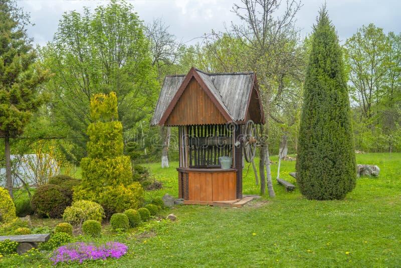 Hölzerner Wasserbrunnen im grünen Park D?nisches Dorf stockfotografie