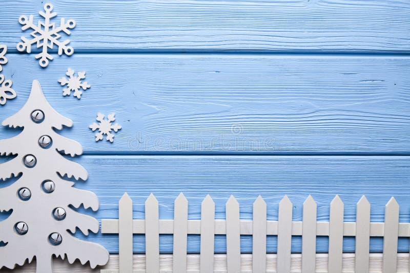 Hölzerner Weihnachtsbaum, Schneeflocken und Zaun auf blauer Tabelle stockfotografie