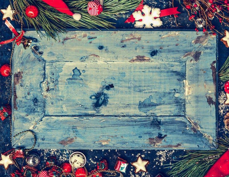 Hölzerner Weihnachtshintergrund im Blau mit den roten und weißen Feiertagsdekorationen, Draufsicht, Rahmen, horizontal stockfoto