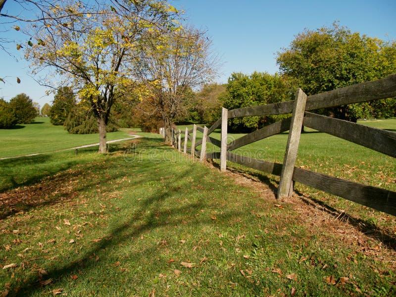 Hölzerner Zaun durch einen gehenden Pfad stockbilder