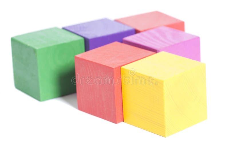 Hölzerner Ziegelsteinmehrfarbenstapel lokalisiert auf Weiß stockfoto
