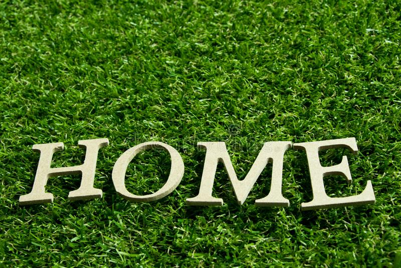 Hölzernes Alphabet im Benennungshaus auf künstlichem grünes Gras backgr stockfotos