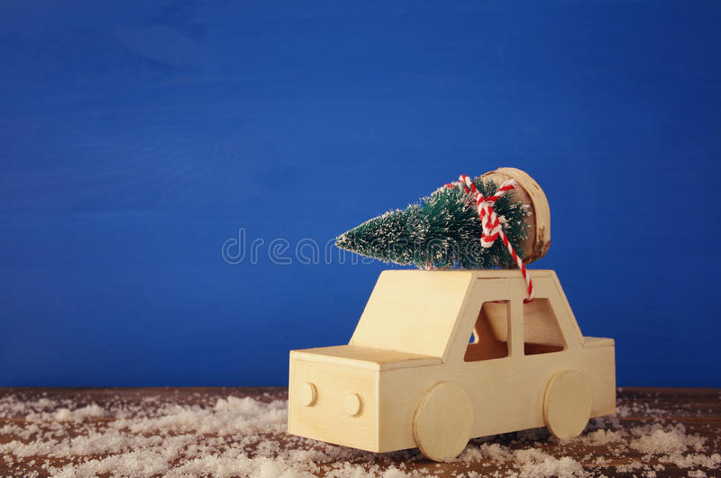 Hölzernes Auto, das einen Weihnachtsbaum transportiert stockbild