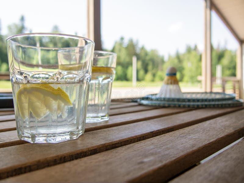 Hölzernes Bauernmöbel auf der Terrasse eines Landhauses Zwei Gläser im Fokus mit einer Auffrischungslimonade mit Zitronenscheiben lizenzfreie stockbilder