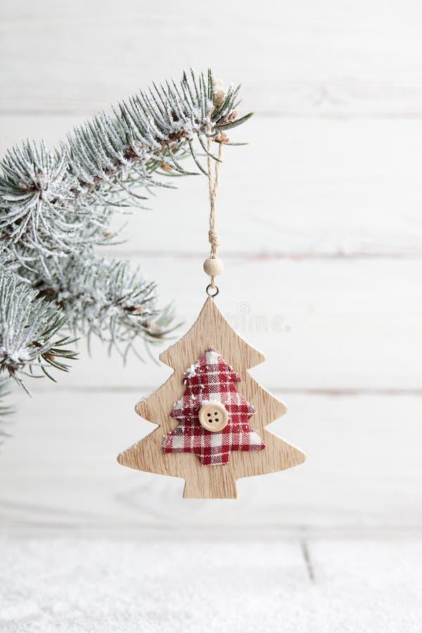 Hölzernes Baum-förmiges Weihnachtsspielzeug, das an der schneebedeckten Niederlassung hängt lizenzfreie stockbilder