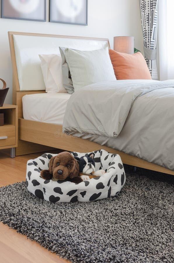Hölzernes Bett mit orange Kissen mit Puppe auf Teppich lizenzfreie stockfotografie