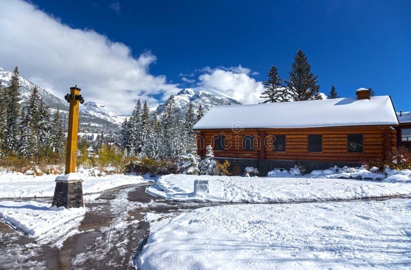 Hölzernes Blockhaus und Snowy-Gehwege in Canmore Alberta Spring Creek Mountain Village stockfotografie