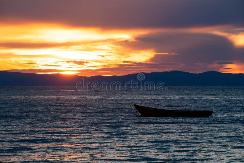 Hölzernes Boot auf dem Baikalsee bei Sonnenuntergang lizenzfreie stockbilder