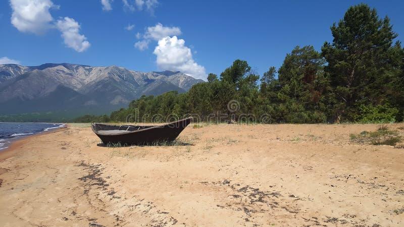 Hölzernes Boot auf dem sandigen Ufer vom Baikalsee lizenzfreies stockbild
