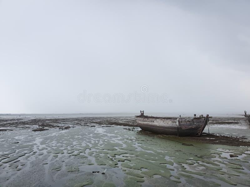 Hölzernes Boot auf den Strand gesetzt zur Ebbezeit auf der Bucht am rainny Tag stockbild