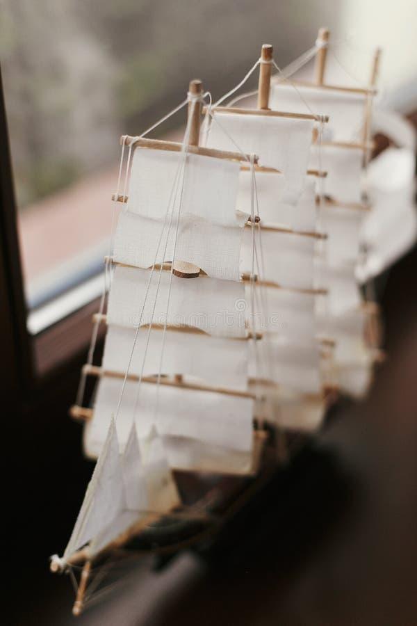 Hölzernes Boot mit zu den Segeln am Fenster Wenig Miniaturfigürchen des Schiffs, hergestellt vom Holz und vom Segeltuch Selektive lizenzfreie stockbilder