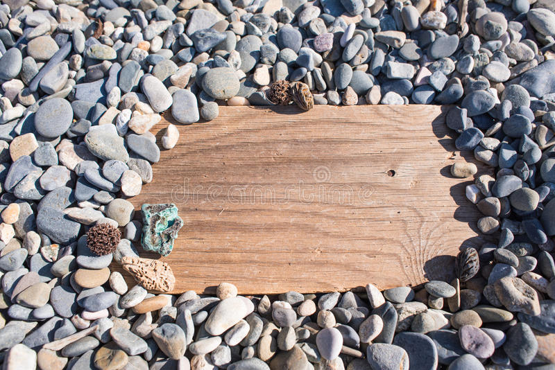 Hölzernes Brett im Stein auf dem Strand Hintergrund, Anschlagtafel, Geröll lizenzfreie stockbilder