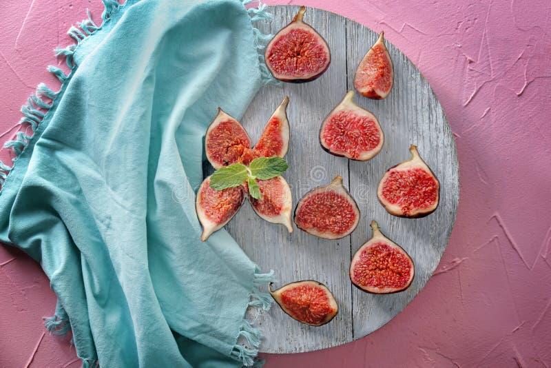 Hölzernes Brett mit frischen reifen purpurroten Feigen auf Farbtabelle, Draufsicht lizenzfreies stockbild