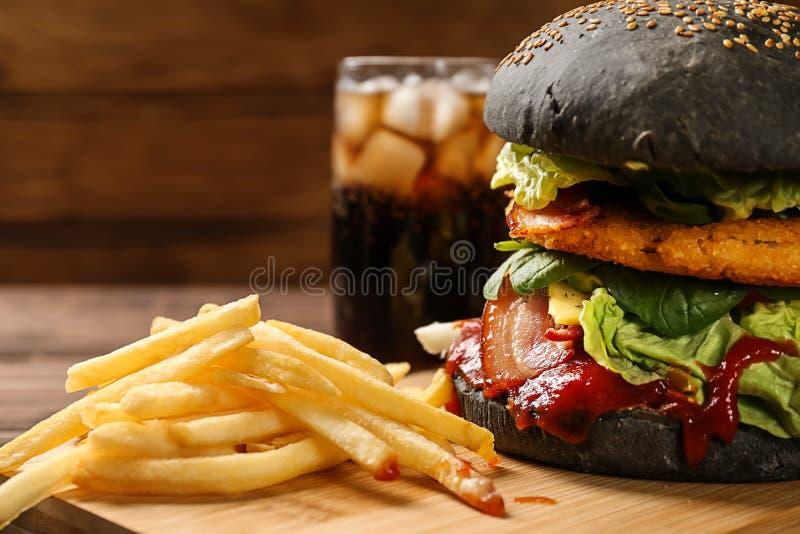 Hölzernes Brett mit geschmackvollem Burger und Pommes-Frites auf Tabelle lizenzfreie stockfotos