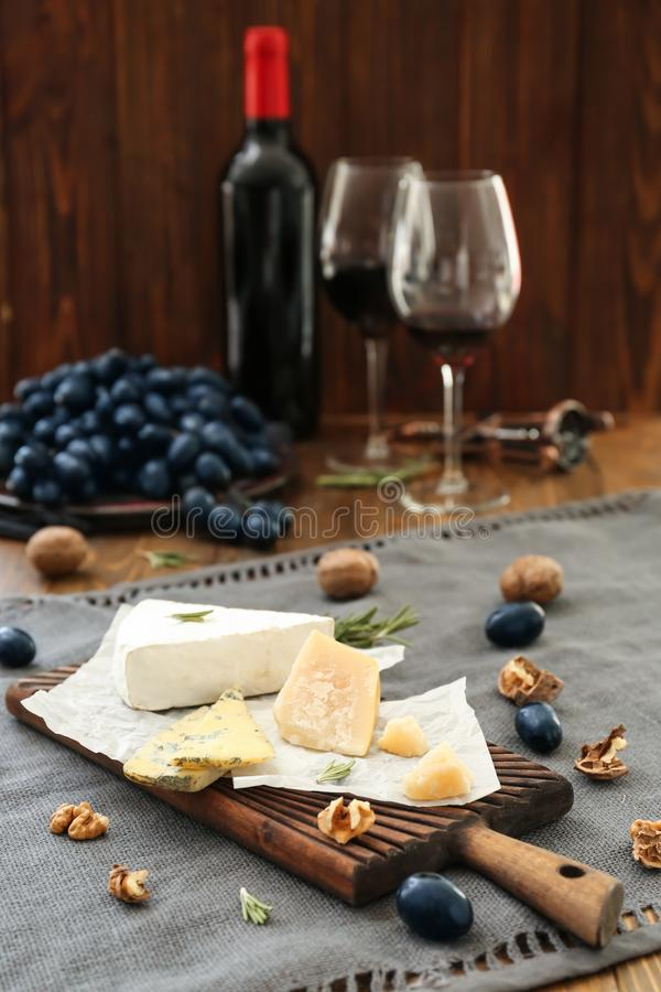 Hölzernes Brett mit verschiedenen Arten des Käses, der reifen Trauben und der Nüsse auf Tabelle stockbild