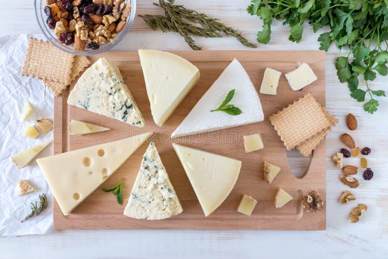 Hölzernes Brett mit verschiedenen Arten des köstlichen Käses mit Nüssen lizenzfreie stockbilder