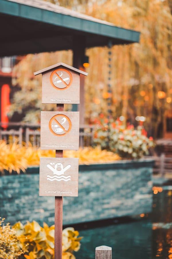 Hölzernes Brett und Nichtraucher unterzeichnen, fischend und schwimmen im Park lizenzfreies stockfoto