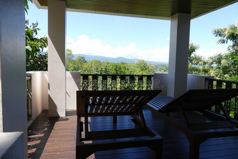Hölzernes deckchair am Balkon mit Wald- und Himmelansicht lizenzfreies stockbild