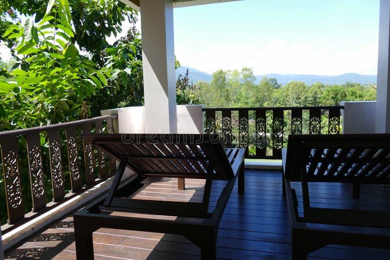 Hölzernes deckchair am Balkon mit Wald- und Himmelansicht stockfotografie