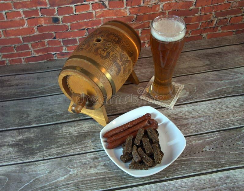 Hölzernes Fass, Glas helles Bier und eine Platte mit Imbissen auf dem Tisch Nahaufnahme stockfotografie