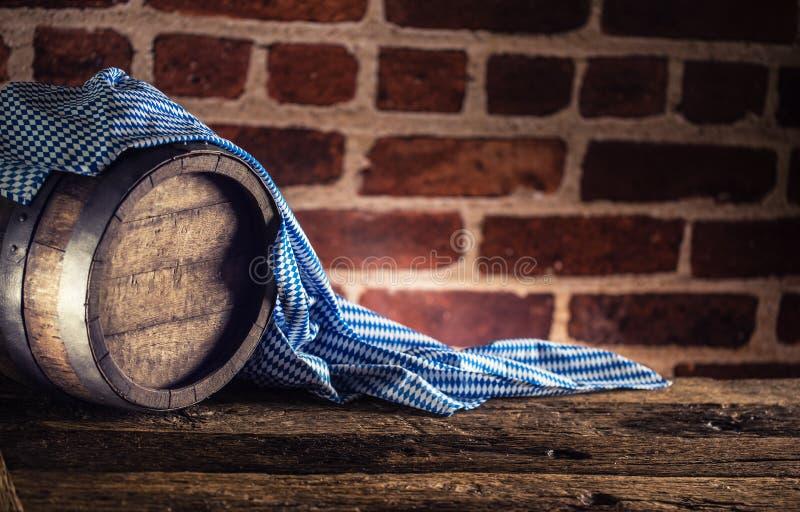 Hölzernes Fass Oktoberfest und blaue Tischdecke auf rustikalem eichenem Tisch stockfoto