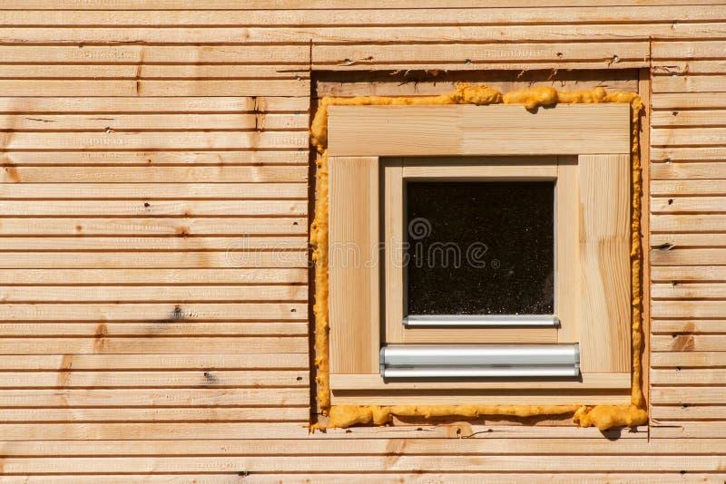 Hölzernes Fenster Schaumfensterisolierung auf hölzernem Bau Bauen eines Öko-Hauses Wärmedämmung stockfotografie
