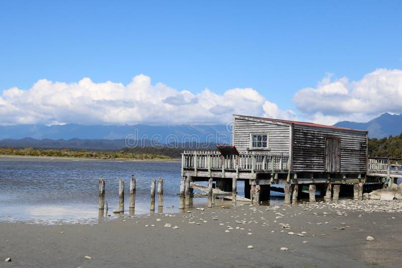Hölzernes Gebäude durch Lagune, Okarito, Neuseeland lizenzfreie stockfotografie