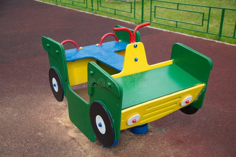 Hölzernes grünes Gelb der Maschine auf dem Spielplatz mit gummierter Beschichtung lizenzfreies stockbild