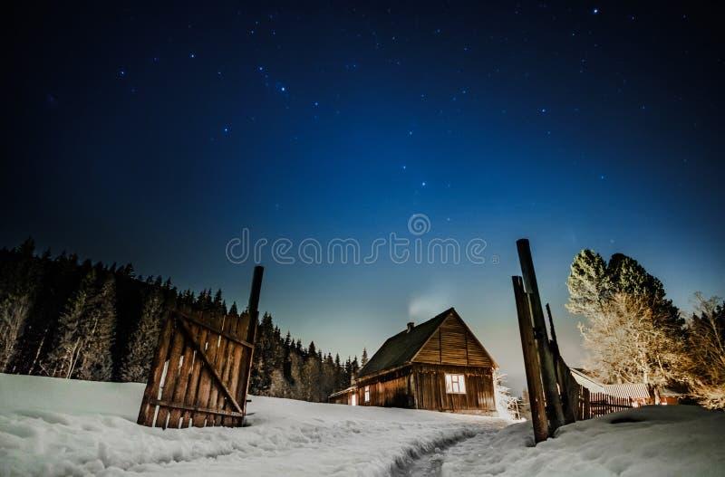 Hölzernes Häuschen mit blauem sternenklarem Himmel nachts lizenzfreie stockfotos