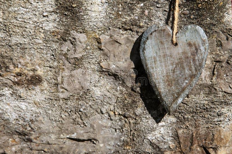 Hölzernes Herz der Grußkarte vor felsigem Hintergrund lizenzfreies stockfoto