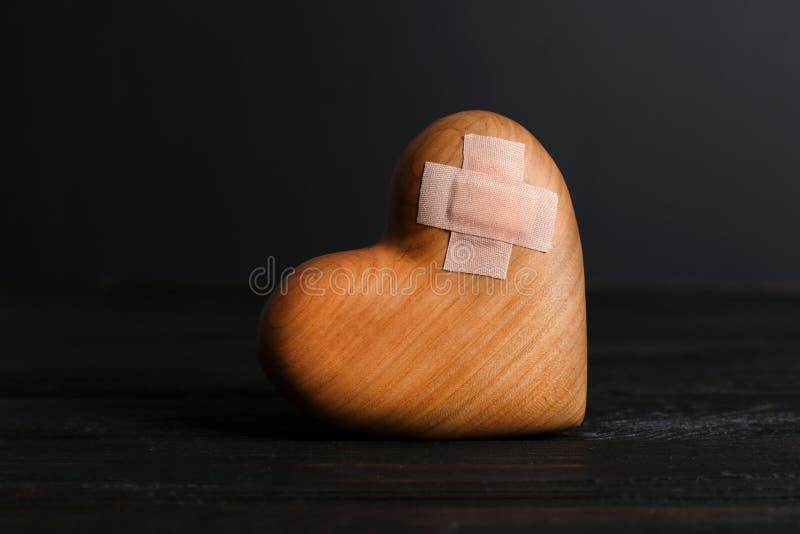 Hölzernes Herz mit Heftpflastern in der Dunkelheit stockfotos