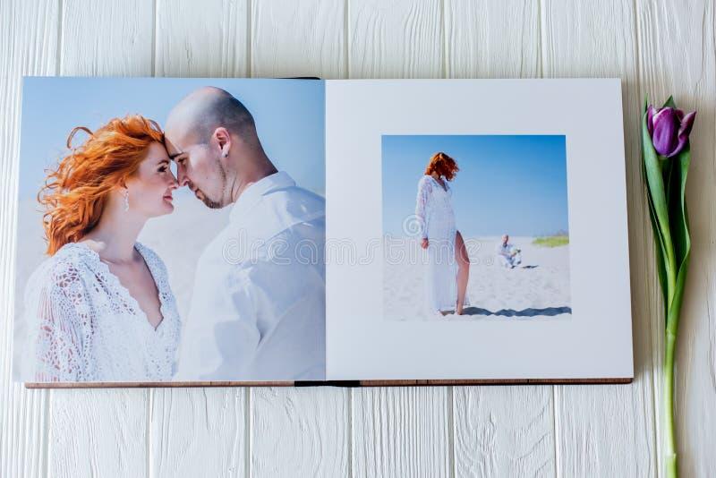 Hölzernes Hochzeitsfotobuch Glückliche junge Paare in der Liebe Braut- und Bräutigamgehen des Hochzeitstags stockbild