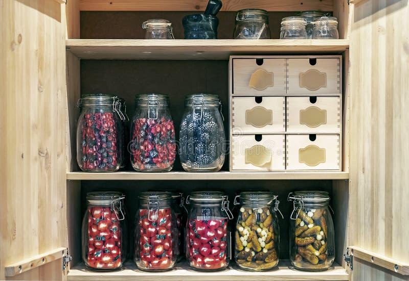 Hölzernes Kabinett mit Glasgefäßen Essiggurken und Marinaden in einer Begriffsart lizenzfreies stockbild