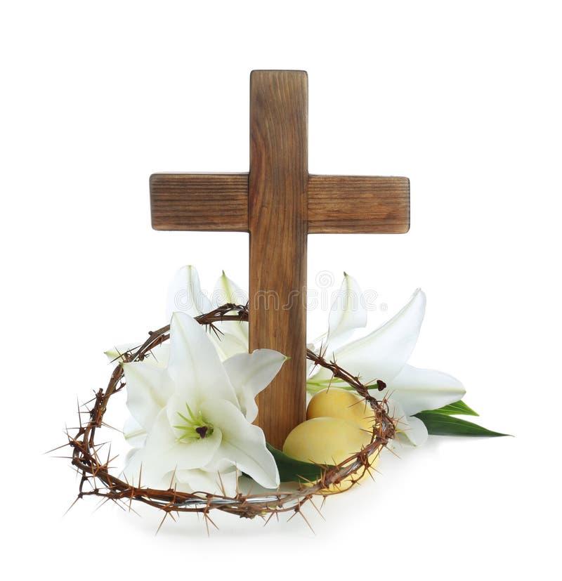 Hölzernes Kreuz, Dornenkrone, Ostereiern und Blütenlilien stockbild