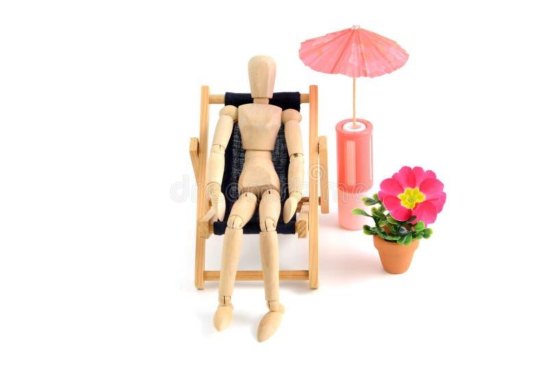 Hölzernes Mannequin, das sunbath im Klappstuhl nimmt stockbild