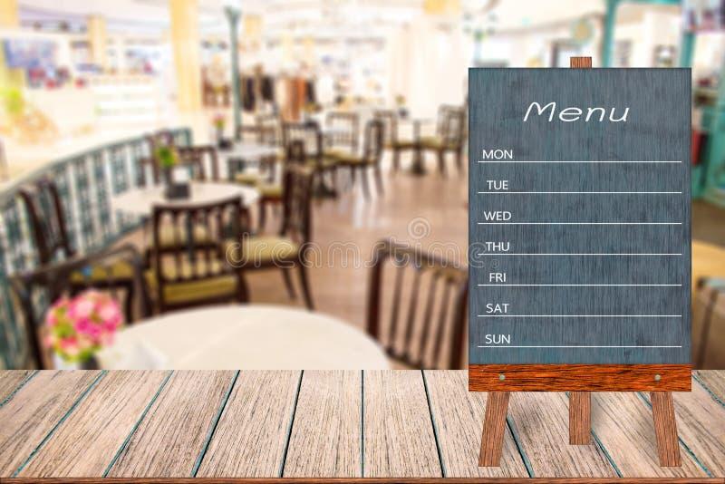 Hölzernes Menüanzeigenzeichen, Feldrestaurantanschlagbrett auf Holztisch, verwischte Bildhintergrund stockbild