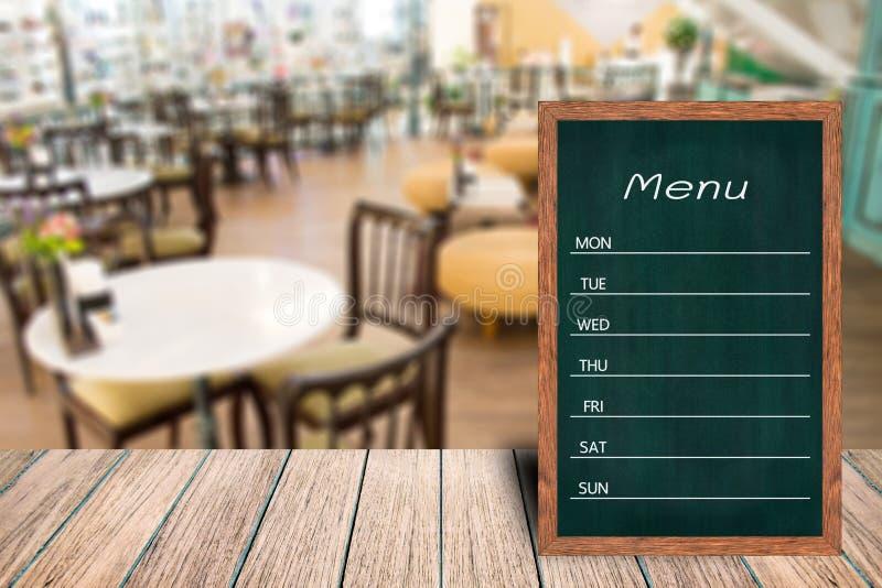 Hölzernes Menüanzeigenzeichen, Feldrestaurantanschlagbrett auf Holztisch, verwischte Bildhintergrund stockfoto
