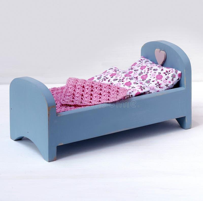 Hölzernes Miniaturbett für Puppe lizenzfreie stockfotografie